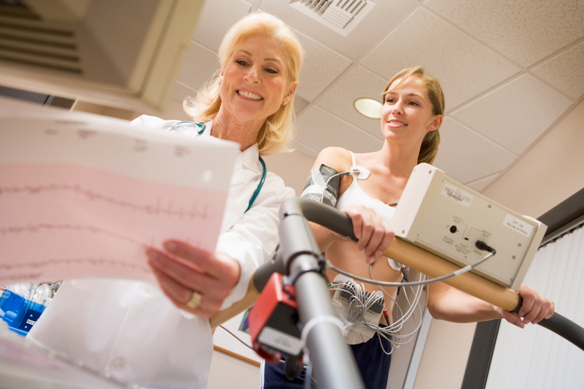 Doctor monitoring heart rate of female patient on treadmill